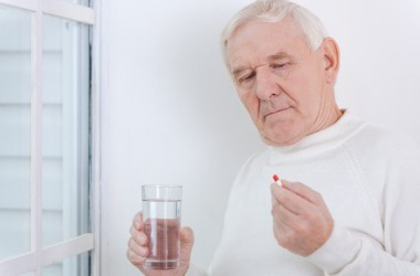 Senior man about to take a blood pressure pill