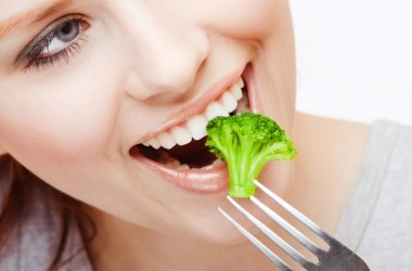 Woman eating disease fighting broccoli off a fork