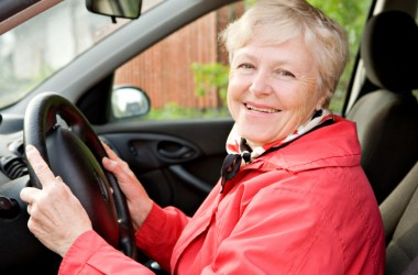 Safe senior driver smiles as she prepares to drive car