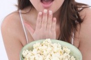 woman eating microwave popcorn a so called healthy food raises her risk of cancer