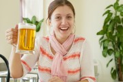 smiling woman holds up a healthy mug of beer