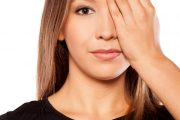 Woman suffering eye twitching covers eye