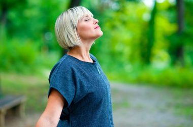 Middle aged woman takes deep breath belly breathing