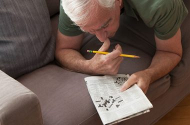 Senior man working on crossword puzzles to fight brain aging