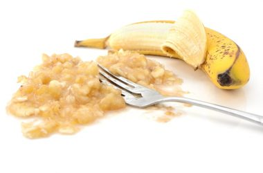 half-peeled banana with a fork in mashed banana is an easy to digest food