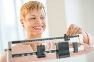 woman on scale happy about her weight loss with no hunger pangs
