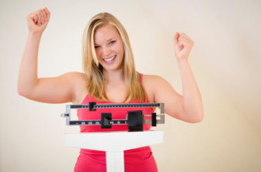 Weight loss. Happy woman on scale lost weight weight loss resolution