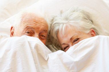 Romantic senior couple with gray hair smiling under covers in bed