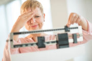 Woman adjusting scale worried about weight gain despite her weight loss diet