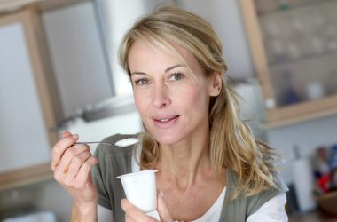 Woman eating dairy yogurt to get enough muscle friendly protein