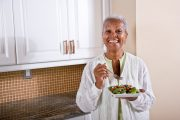 Mature woman eating salad in kitchen