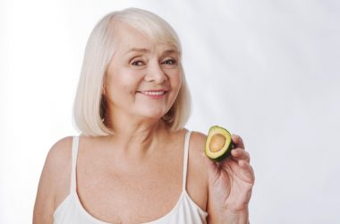 Mature smiling woman holding a mood boosting avocado half