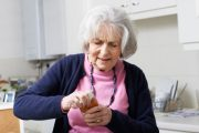 Senior woman with vitamin D deficiency struggling to take lid off jar