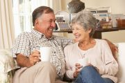 Senior couple sitting on sofa enjoying black tea health benefits