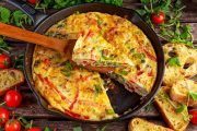 A frittata in a cast iron pan stuffed with healthy vegetables