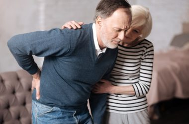 Senior man holding back is having sciatica pain