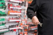 Strange symptoms. Senior man shoplifting a wrench from a hardware store