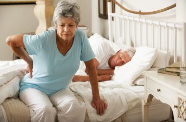 Senior woman waking up in pain from wrong sleeping
