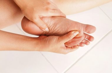 Woman massages achy swollen feet which is among most common foot problems