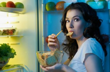 Woman sneaking snacks from open fridge because she feels hungry all the time