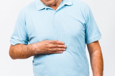 MMan with heartburn holds stomach and considers taking a risky proton pump inhibitor PPIs