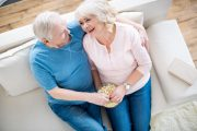 Senior couple sitting on sofa eating popcorn to sleep better