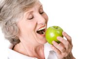 Smiling senior woman bites into a green apple boosting her happiness