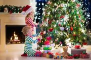 Children decorating lit Christmas tree in living room