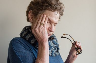 Older woman rubbing eyes suffers from the fatigue of chronic inflammation