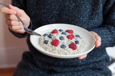 Woman eats one of the best breakfast foods steel cut oatmeal with berries