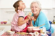 Grandmother and grandchildren laughing and baking in kitchen