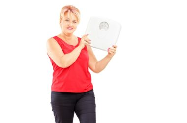 Senior woman holds scale to show successful weight loss without counting calories