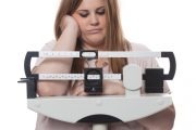 Overweight woman looking at scale trouble losing weight and weight loss