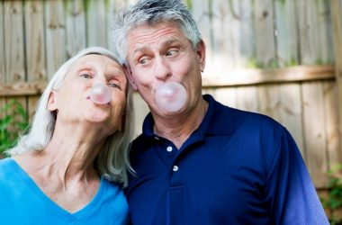 Silly senior couple blowing chewing gum bubbles for more calorie burn.