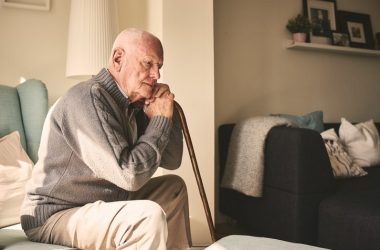 Elderly man sitting alone at home feeling loneliness