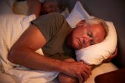 Senior man asleep in bed lowering heart disease risk and heart risk