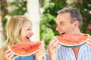 Smiling senior couple eating watermelon a summer foods which is slimming