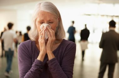 Senior woman with mucus buildup and runny nose symptoms blowing nose