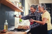 Smiling older couple cook and add spices to food to boost metabolism