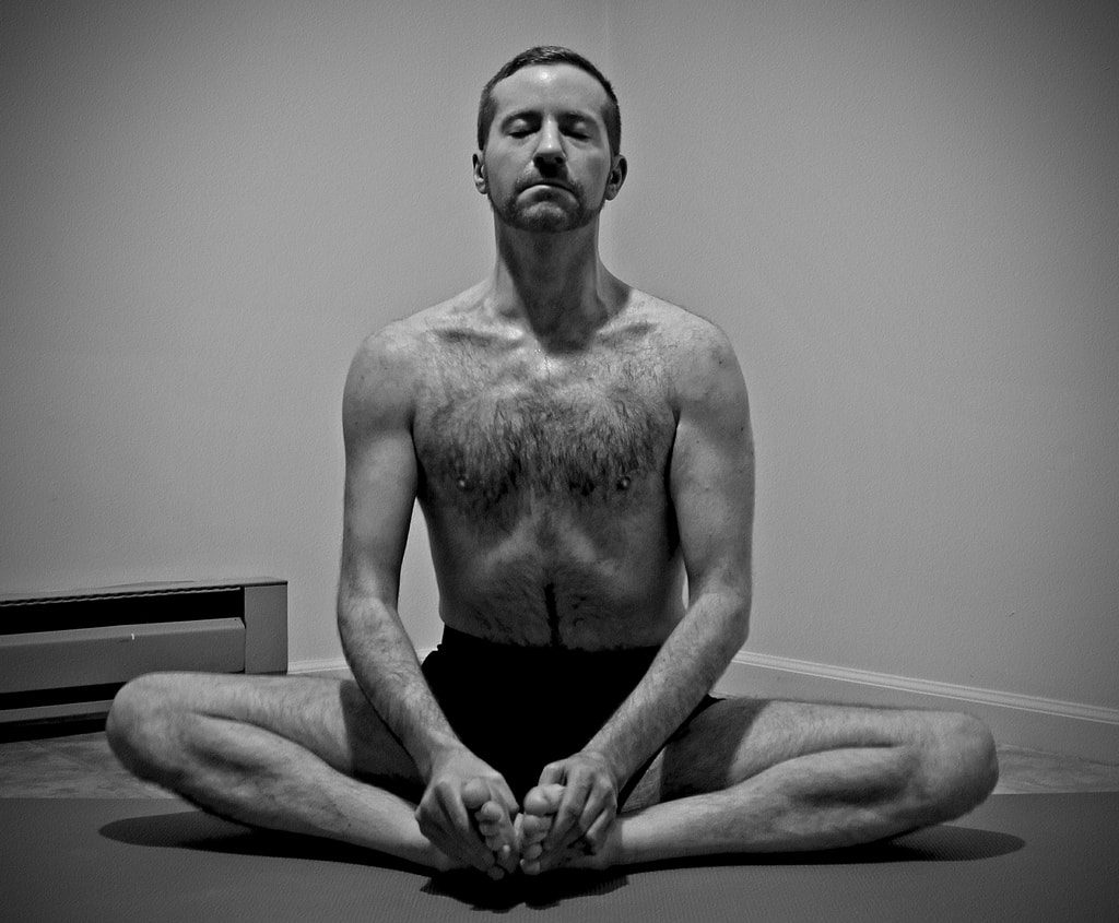 Yoga man performing Bound Angle Pose