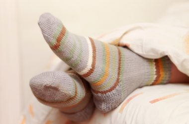 Feet wearing socks in bed which can help you fall asleep