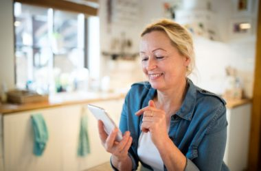 Senior woman with smartphone being exposed to vision damaging blue light