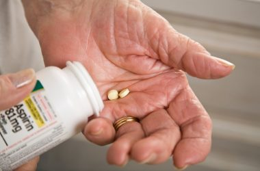 Senior woman with aspirin in hand facing hidden dangers from blood thinner