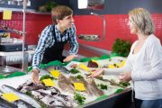 Smiling female customer buying fish high in memory boosting omega-3