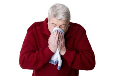 Senior man sneezing from winter allergies