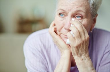 Depressed senior woman holding tissue to eye