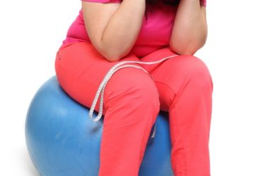 Frustrated woman sitting on exercise ball