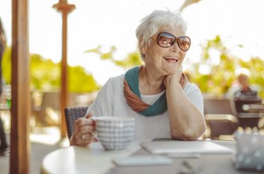 Happy smiling senior woman drinking coffee to live longer