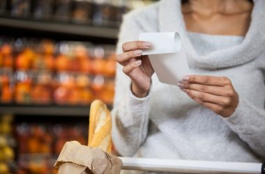 Mid section of woman holding a store receipt