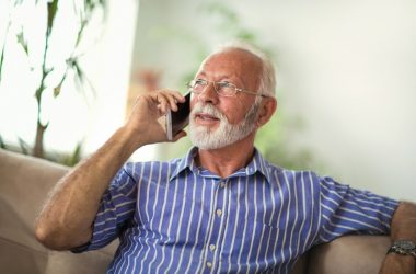 Senior man chatting on a 5G cellphone at home